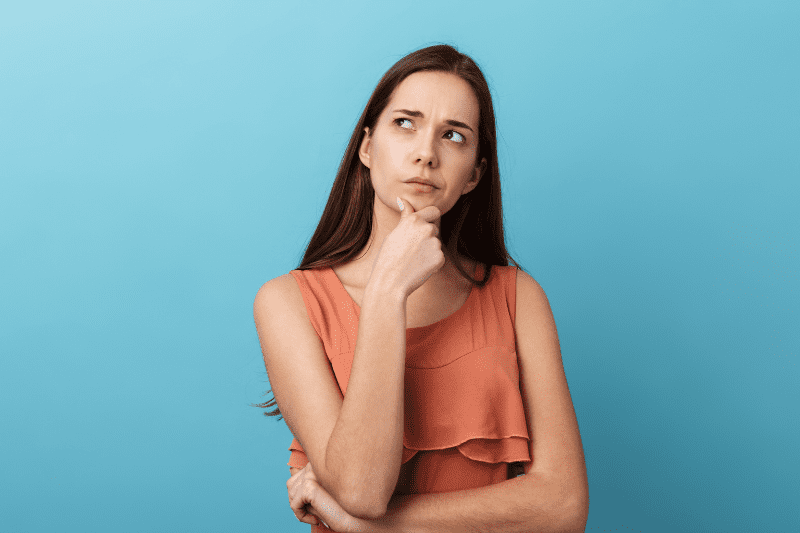Confused woman thinking and looking into distance